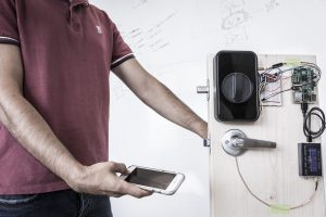 "UW engineers use a smartphone to send a secure password through the human body and open a door with an electronic smart lock. These ""on body"" transmissions employ low-frequency signals generated by the phone's fingerprint sensor. Photo credit: Mark Stone/University of Washington"
