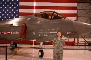 EE Ph.D. student, Katherine Pratt, is pictured with a F-35 Joint Strike Fighter. Pratt is a U.S. Air Force Veteran. Credit: Katherine Pratt via KUOW.