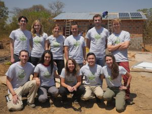 Henry Louie (top row, third from right) and his KiloWatts for Humanity volunteers stand in front of a solar-powered energy kiosk they built in Zambia.