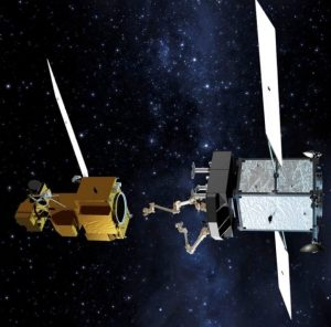 An artist's conception shows one satellite extending its robotic arm to grasp and refuel another satellite in orbit