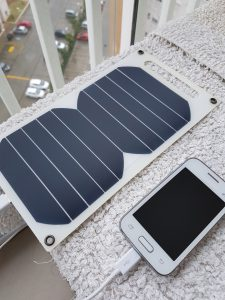 Small solar panels powering a plugged-in cell phone