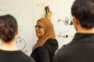 woman writing equations on white board while two students watch