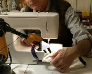 man sewing a mask with help from a robotic device