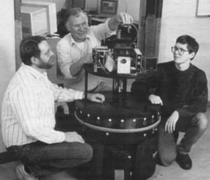 Three men squatting around a mobile robot