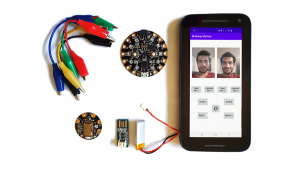 Photo of an Android smartphone, an Arduino microcontroller board, a Bluetooth Low Energy shield, alligator clips, a battery and a charger.