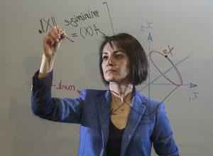 Maryam Fazel writing equations on a glass wall