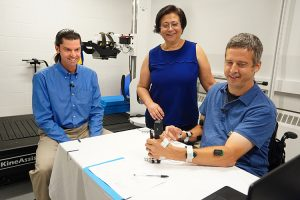 CNT researchers Chet Moritz and Dr. Fatma Inanici work with study participant on grip strength