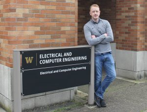 Cody Brereton standing next to the UW ECE sign outside the Paul Allen Center