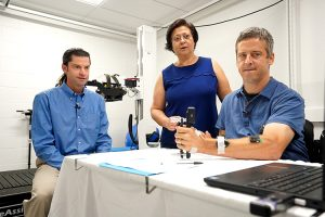 Chet Moritz and Dr. Inanici watch study participant Jon Schlueter complete a grip-test